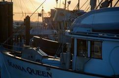 在船坞的商业捕鱼业小船落日的 免版税库存照片