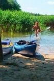 在船坞的小船,有桨的快乐的女孩在他的手上 库存照片