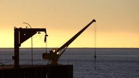 在船坞的老起重机在智利的码头的日落的 库存图片