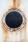 在船墙壁上的圆的生锈的舷窗 免版税图库摄影