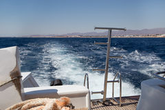 在船尾地泡沫海上的一艘移动的船 库存照片