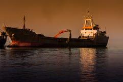 在船的吊斗装运机在Riprap工作 免版税库存照片