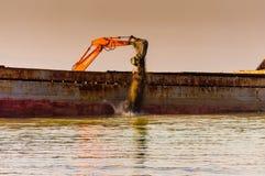 在船的吊斗装运机在Riprap工作 库存图片