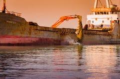 在船的吊斗装运机在Riprap工作 免版税库存图片