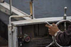 在船舵轮子葡萄酒小船特写镜头的手 免版税库存图片