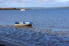 在船锚的小蓝色划艇 库存图片