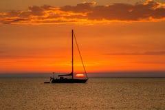 在船锚的风船有美好的日落的在背景中 免版税库存图片