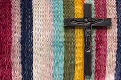 在色的地毯背景的黑木耶稣受难象 免版税库存照片
