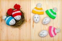 在色的盖帽的复活节彩蛋在一张木桌上,激动人面 库存图片