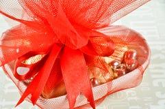 在色的箔包裹的巧克力包装与红色丝带 免版税图库摄影