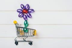 在色的箔包裹的微型复活节彩蛋形成一朵花,在购物车 春天销售,复活节销售概念 库存图片