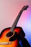 在色的背景的声学吉他 免版税库存照片
