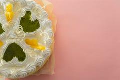 在色的背景的白蛋糕与从上面被射击的丝带 库存照片