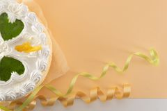 在色的背景的白蛋糕与从上面被射击的丝带 库存图片