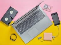 在色纸背景的现代数字式小配件,存储介质, devaysy和过时模式媒介设备 顶视图 平的位置 免版税图库摄影