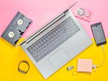 在色纸背景的现代数字式小配件,存储介质, devaysy和过时模式媒介设备 顶视图 免版税库存图片