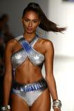 在艺术学院的时装表演期间,模型增光在设计师游泳服装的狭小通道 免版税库存照片