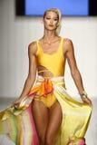 在艺术学院的时装表演期间,模型增光在设计师游泳服装的狭小通道 免版税库存图片