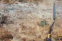 在艺术家帆布的调色刀与棕色油漆涂层  库存照片