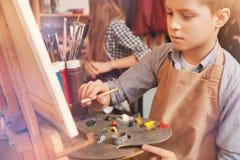 在艺术帆布的严肃的年轻男孩绘画 免版税库存照片
