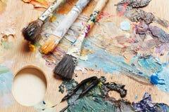 在艺术性的pallette的三支使用的画笔 免版税库存图片