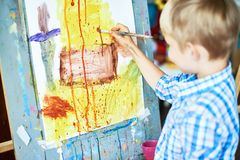 在艺术疗法的小男孩绘画 免版税图库摄影