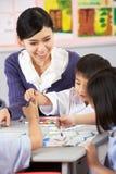 在艺术课期间的教师帮助的学员 库存照片