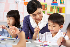 在艺术课期间的教师帮助的学员 免版税库存照片