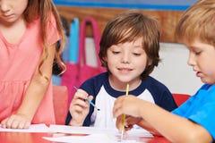 绘在艺术课的孩子在学校 免版税库存图片