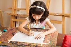 在艺术课的小女孩图画 库存照片