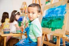 在艺术课的拉丁男孩绘画 免版税库存照片