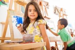 在艺术课的西班牙女孩绘画 库存照片