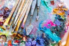 在艺术调色板的明亮的混杂的颜色油漆有油漆刷的 库存照片