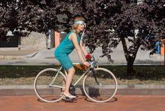 在节日减速火箭的巡航期间,循环在城市的葡萄酒衣物的活跃妇女停放 免版税库存照片
