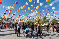 在节日期间,走在气球装饰下的人人群在城市停放 库存图片