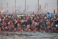 在节日Kumbh Mela期间,印度献身者走向恒河的合流圣洁垂度的 免版税库存图片