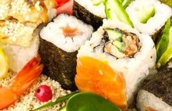 在芝麻籽的寿司与绿色叶子 库存照片