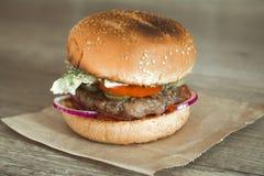 在芝麻小圆面包的汉堡包用多汁牛肉小馅饼和新鲜的沙拉成份在被弄皱的包装纸在一张土气木桌上 免版税库存图片