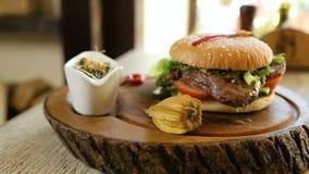 在芝麻籽小圆面包的水多的牛肉汉堡包膳食冠上了用烟肉和乳酪并且服务用酥脆炸薯条 股票录像