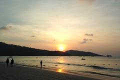 在芭东区海滩的日落,在海反射了,反对山的背景,泰国 库存图片