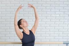 在芭蕾演播室的芭蕾舞女演员实践的舞蹈在纬向条花,特写镜头画象附近 免版税库存照片