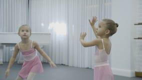 在芭蕾类期间,两个女孩做树干转弯处用rasing的手 股票录像