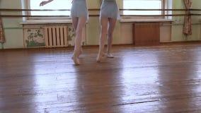 在芭蕾类期间,蓝色紧身连衣裤的芭蕾舞女演员做在对的锻炼 股票录像