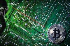 在芯片的银色Bitcoins 下来趋向 绿色背景 安全土窖  库存照片