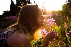 在花中的一个晴朗的草甸,在一美丽晴朗,夏天和温暖的天,女孩从流程的气味得到轻触 图库摄影