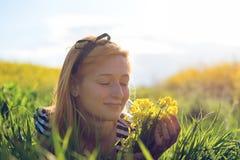 在花中间的领域的逗人喜爱的女孩 免版税库存照片