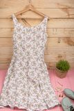 在花卉图案的礼服在挂衣架、蓝色鞋子和珍珠首饰垂悬:项链,头发珍珠夹子,在木背景的耳环 免版税库存照片