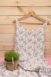 在花卉图案的礼服在挂衣架和珍珠首饰垂悬:项链,头发珍珠夹子,在木背景的耳环 免版税图库摄影