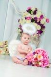 在花和竖琴背景的一点天使微笑和愉快的开会  免版税库存照片