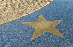 在花岗岩地板上的古铜色星 库存照片